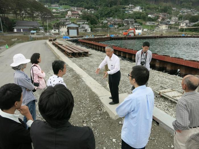 Community leader Shinatro Suzuki explaining the seawall plans